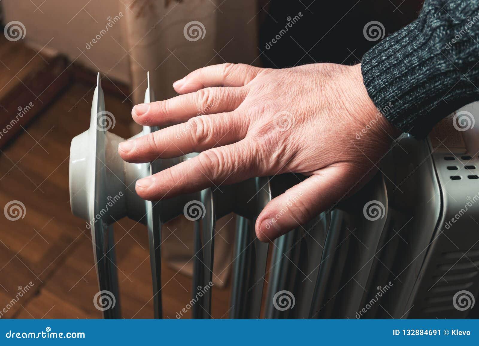 Mężczyzna sprawdza temperaturę elektryczny nafciany nagrzewacz z jego ręką W poza sezonem, środkowym ogrzewaniu, zawsze no pracuj