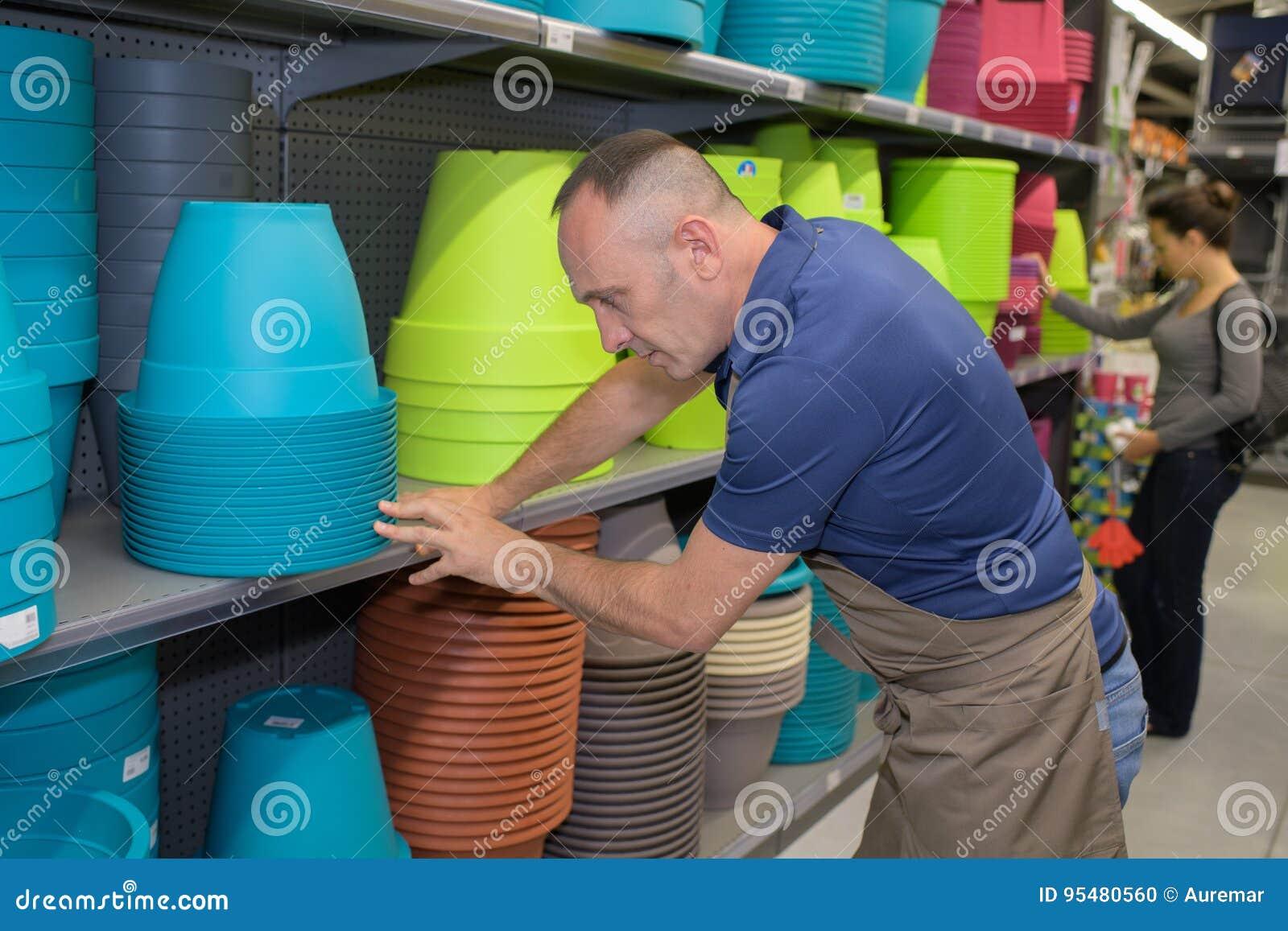 Mężczyzna sprząta w górę kolorowych garnków przy shope