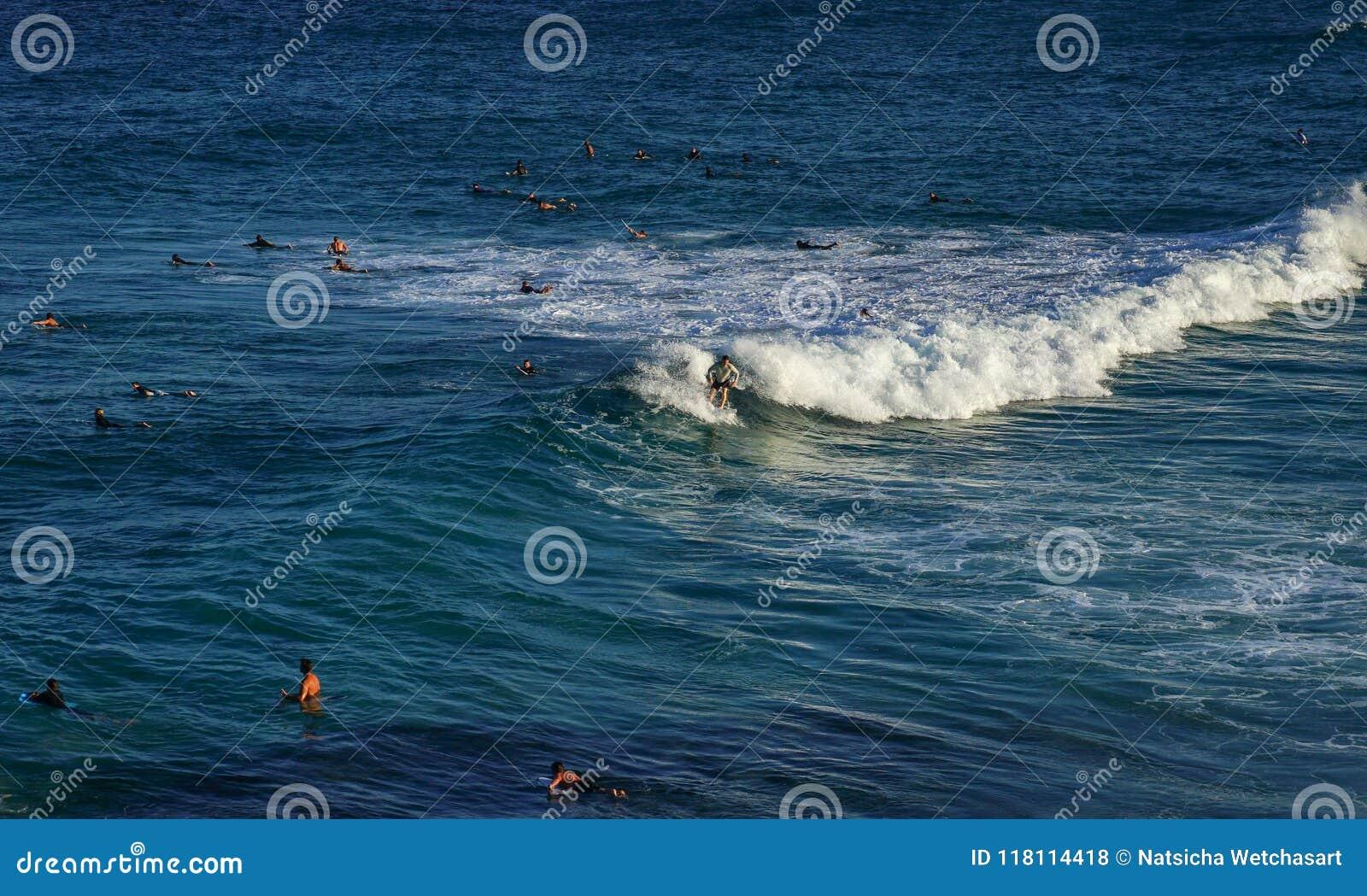 Mężczyzna surfing na biel piany fala w błękitnym oceanie z ludźmi pływać