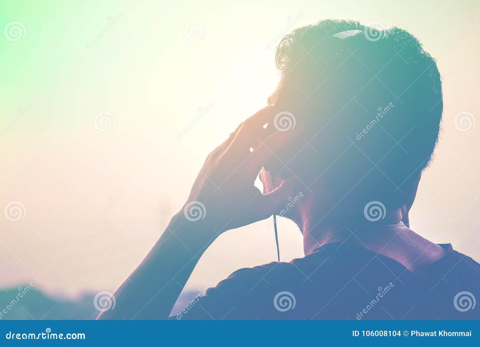 Mężczyzna sylwetka słucha hełmofony na zmierzchu krajobrazu tle