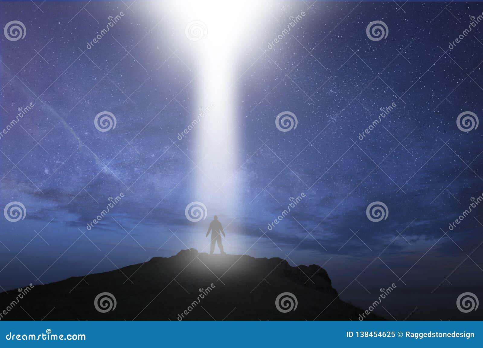 Mężczyzna sylwetkowy, pozycja na górze wzgórza z UFO lekkiego promienia nadchodzącym puszkiem przy nocą