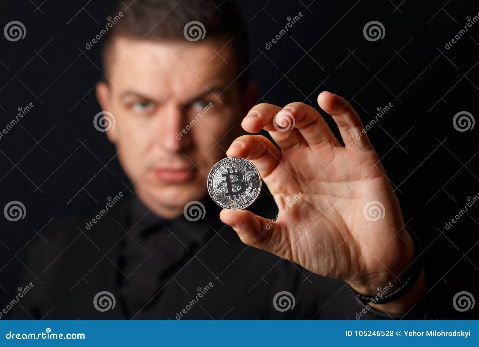 Mężczyzna trzyma bitcoin