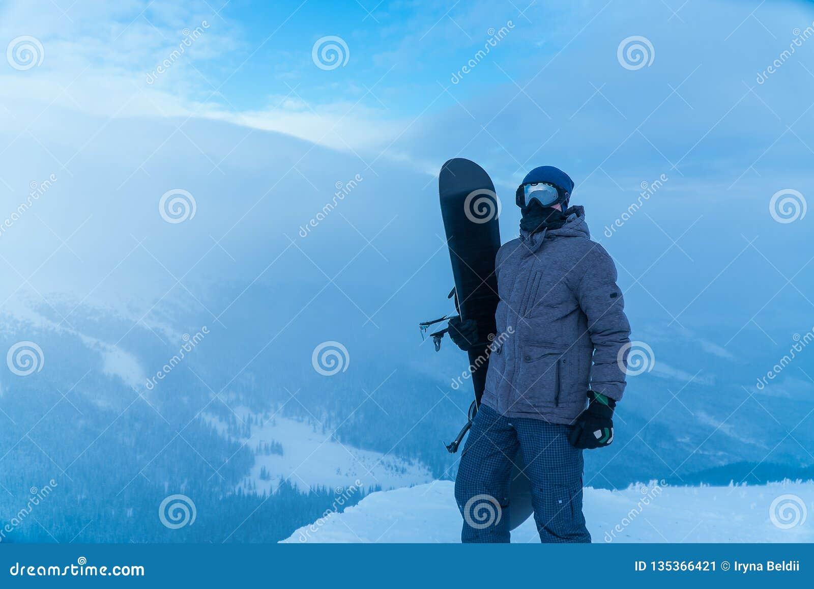 Mężczyzna trzyma snowboard w ręce Snowboarder w górach