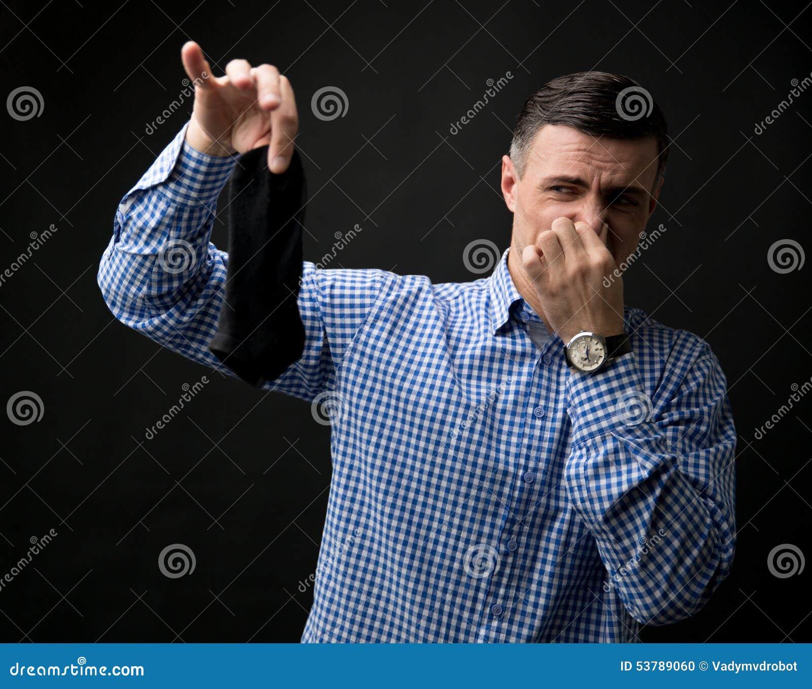 Mężczyzna trzyma zaśmierdłe skarpety i zatykającego nos