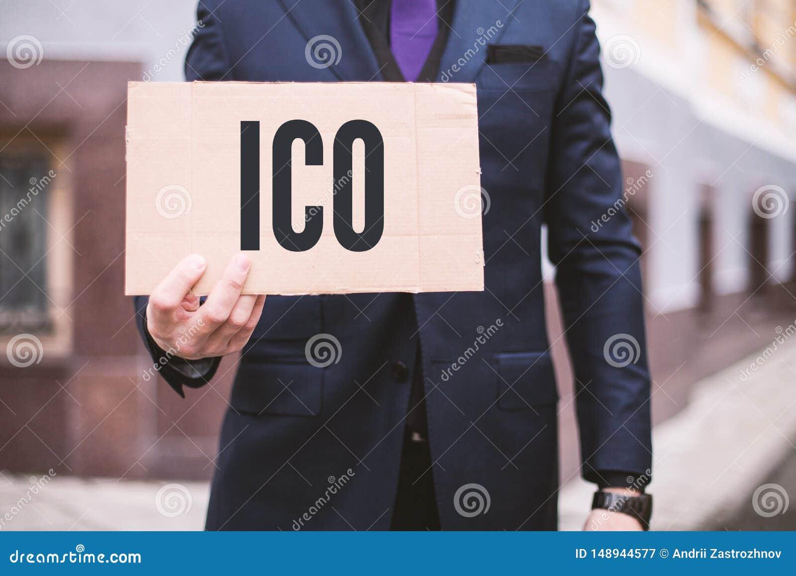 Mężczyzna trzyma znaka w jego ręce z inskrypcji «ICO «inicjałem Menniczy Offerering Cyfrowego handlu rynku Elektroniczny zapas In