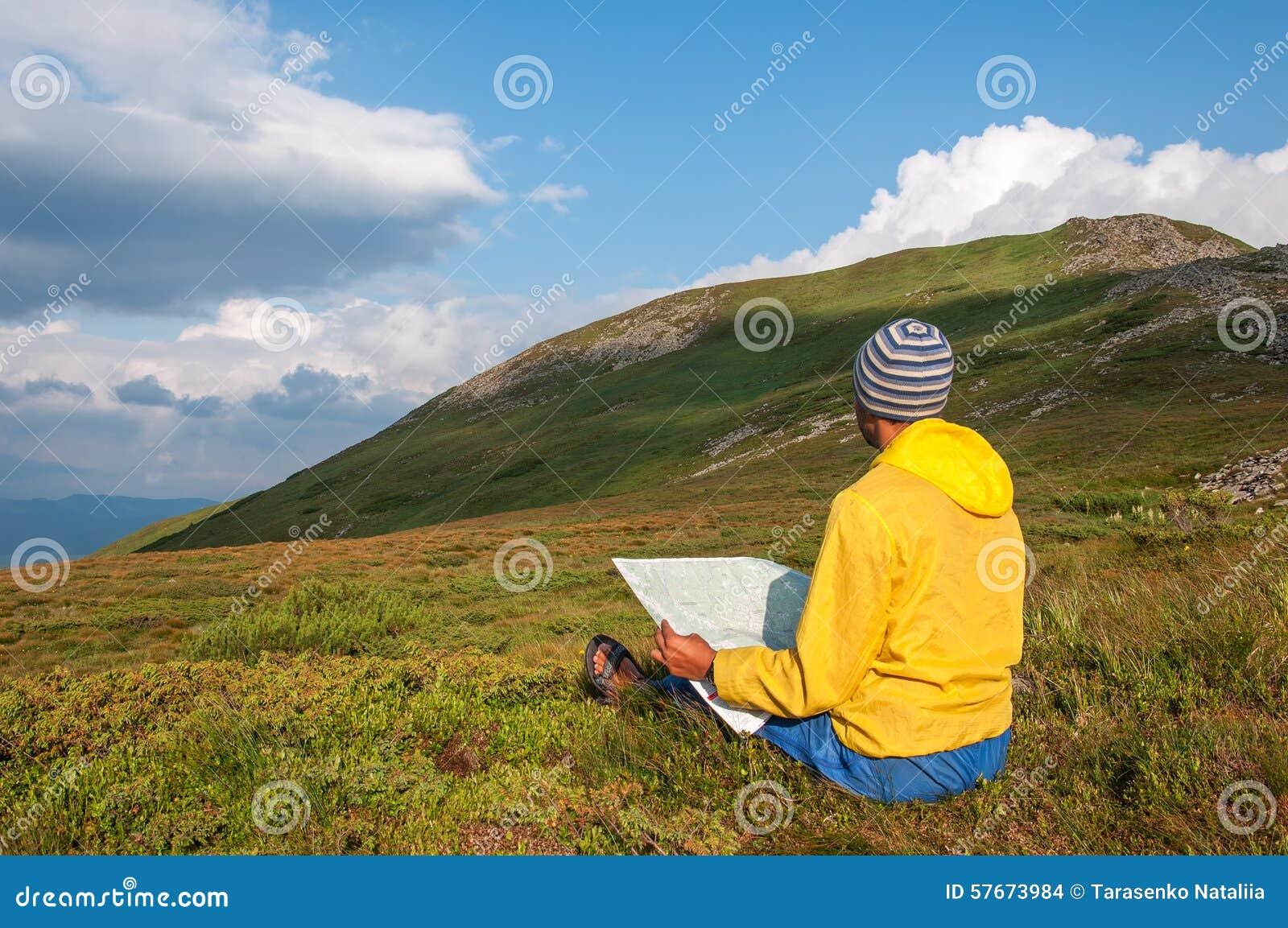 Mężczyzna turysta w górze czyta mapę