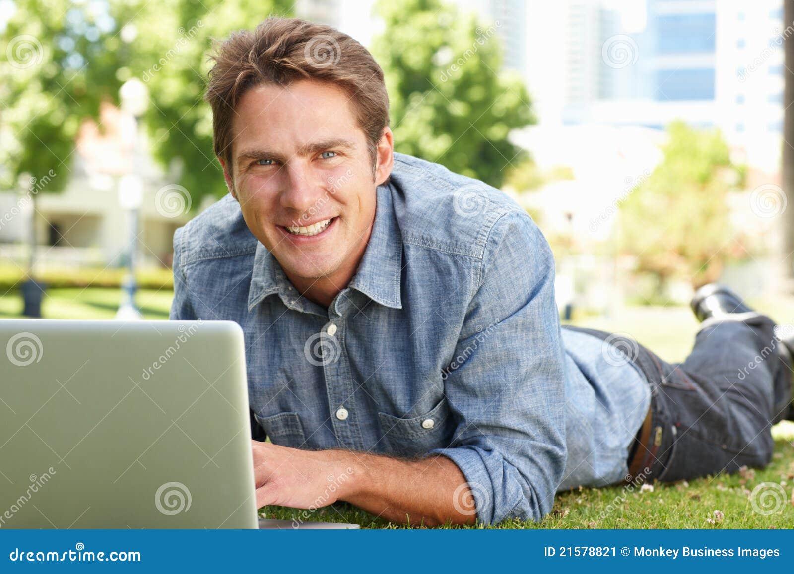 Mężczyzna używać laptop w miasta parku