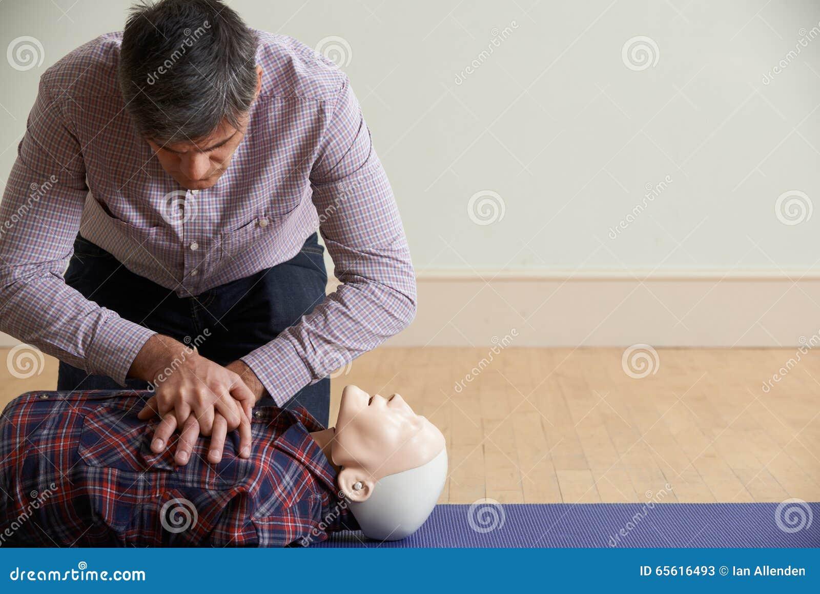 Mężczyzna Używa CPR technikę Na atrapie W pierwszej pomocy klasie