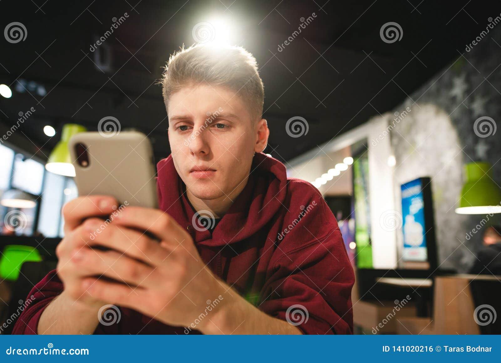 Mężczyzna używa smartphone w fast food kawiarni, skupia się na patrzeć smartphone ekran przeciw tłu kawiarnia