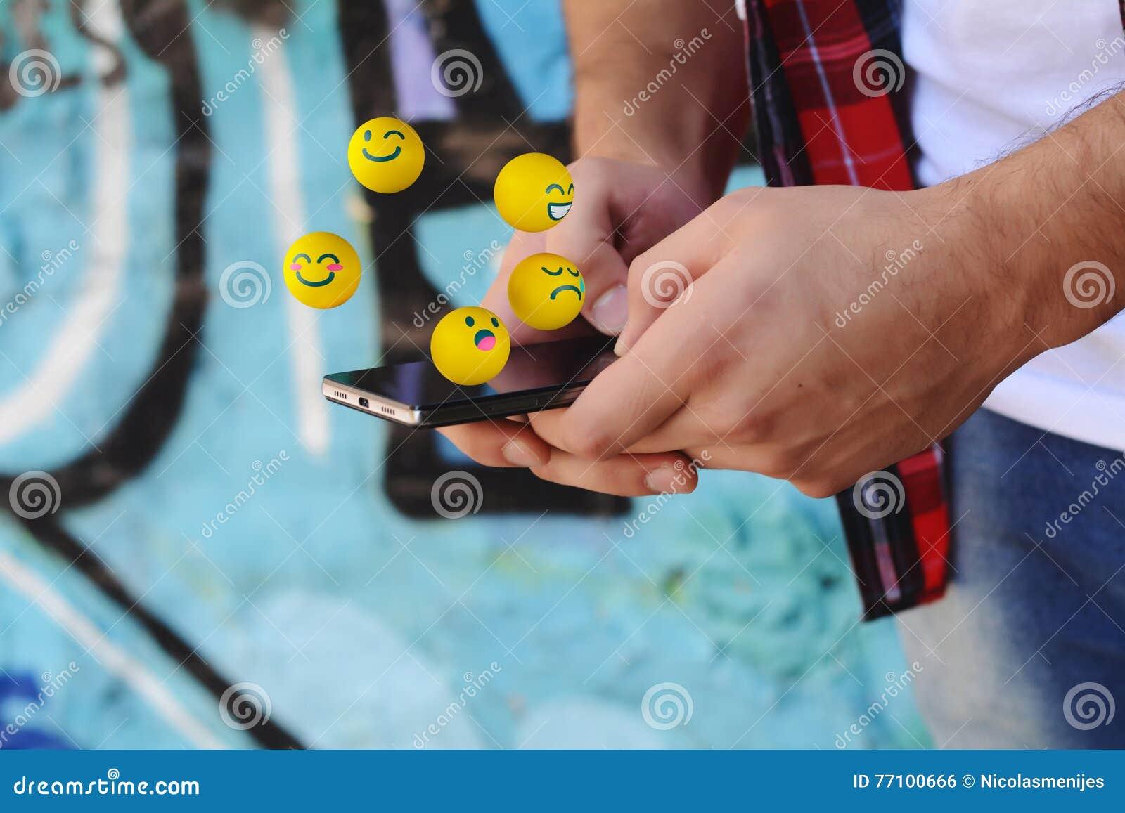 Mężczyzna używa telefonu dosłania emojis