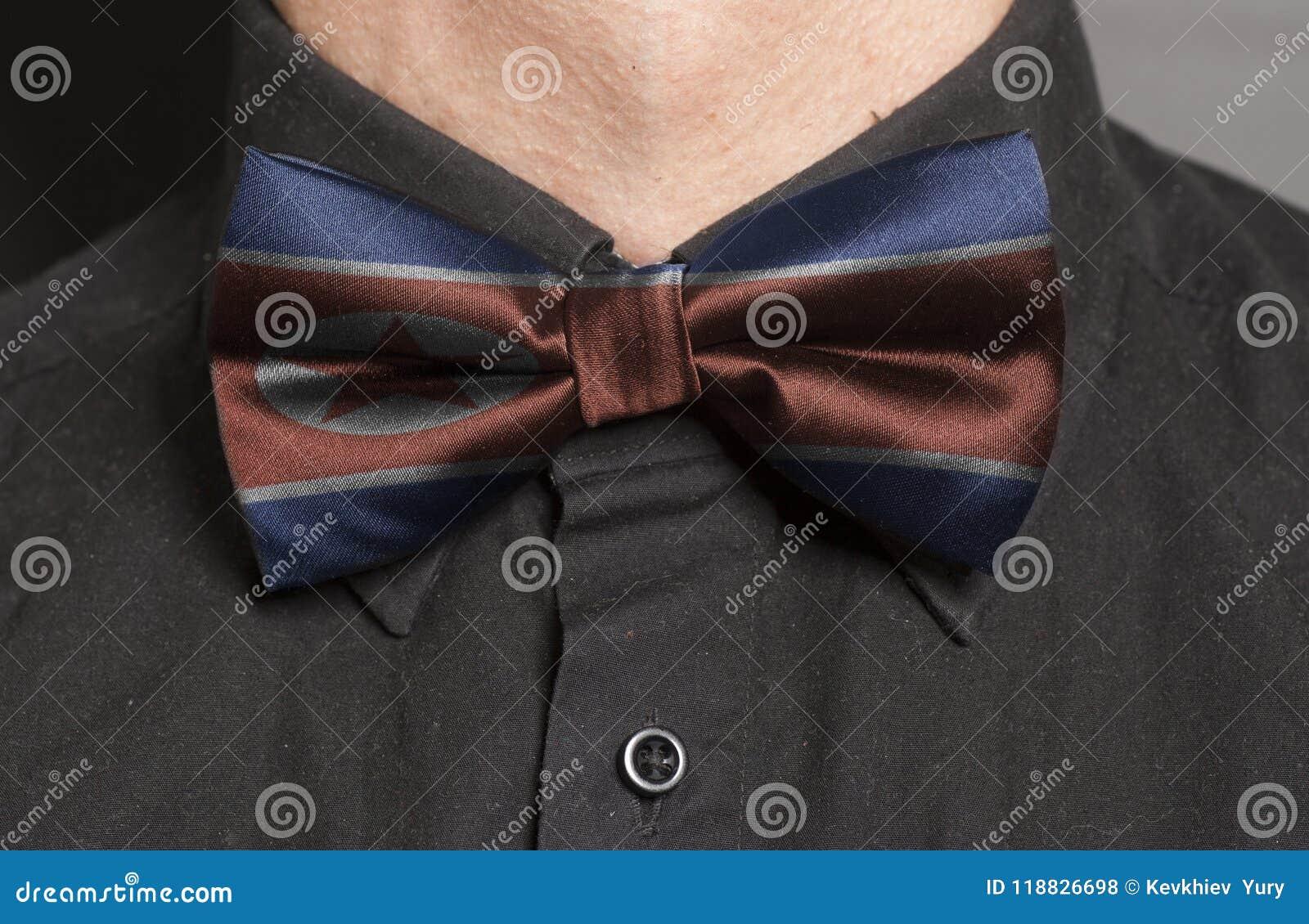 Mężczyzna Ubierająca Czarna koszula Z łęku krawatem z flaga Północny Korea