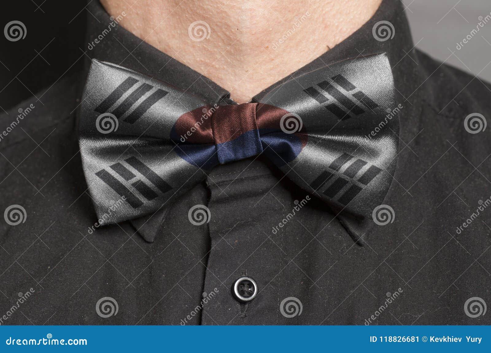 Mężczyzna Ubierająca Czarna koszula Z łęku krawatem z Poludniowo-koreańską flaga