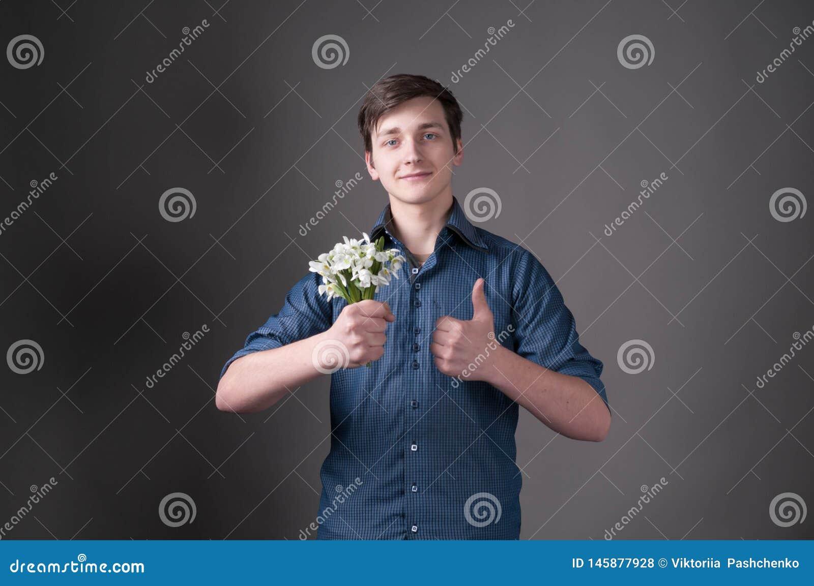 Mężczyzna w błękitnym koszulowym mienie bukiecie z śnieżyczkami patrzeje kamerę i thumbing w górę popielatego tła na,