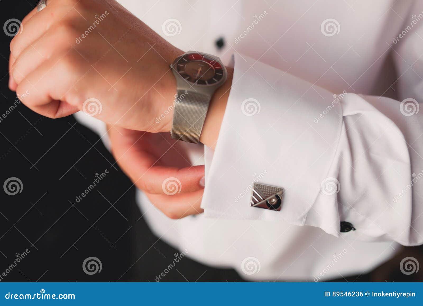 Mężczyzna w białej koszula w okno stawia dalej cufflinks