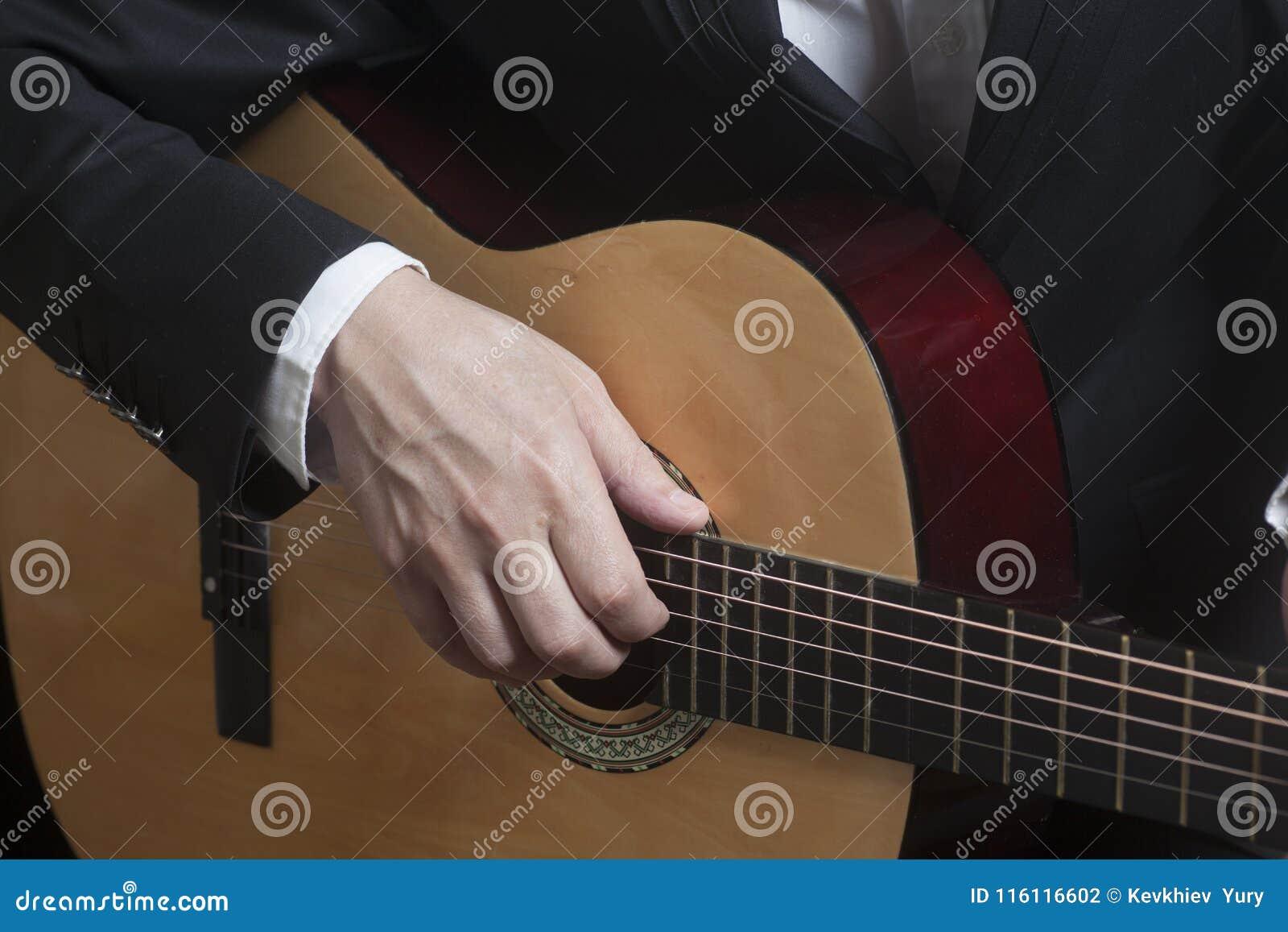 Mężczyzna w czarnym kostiumu z akustyczną klasyczną gitarą