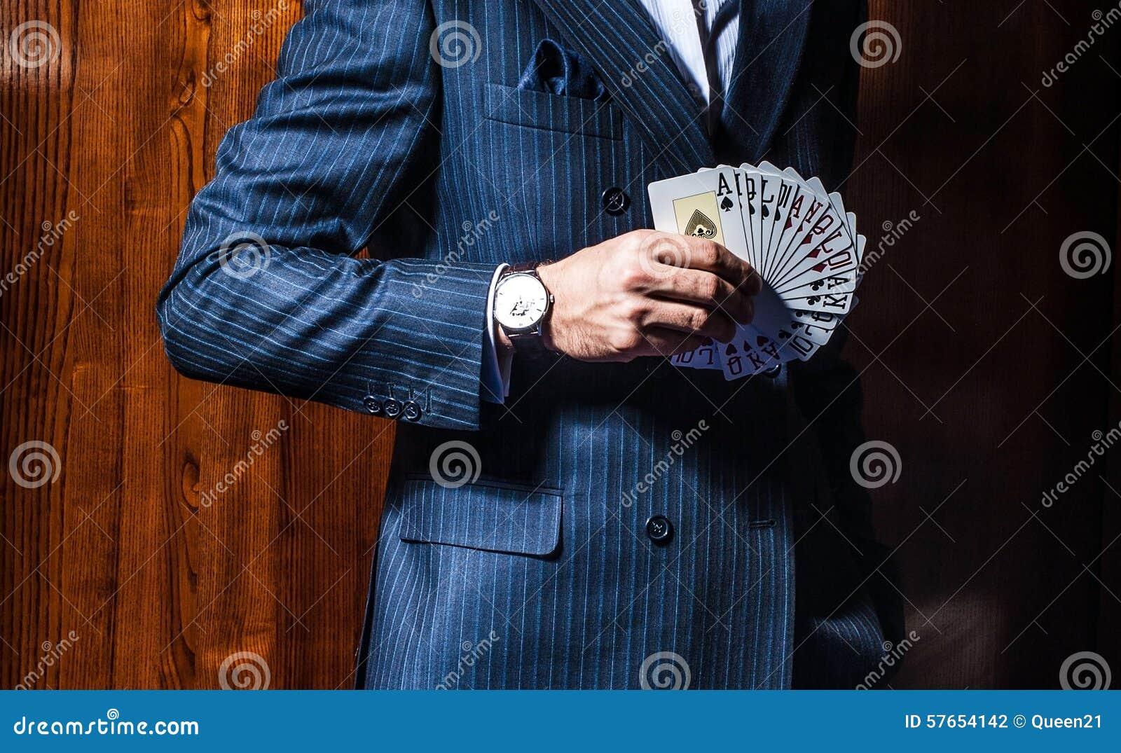 Mężczyzna w kostium pozach z kartami na drewnianym tle