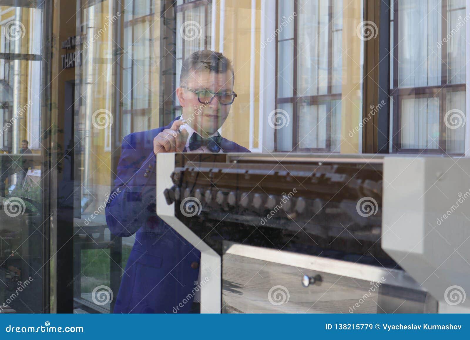 Mężczyzna w kostiumu błękitnych spojrzeniach przy drukową prasą za szkłem