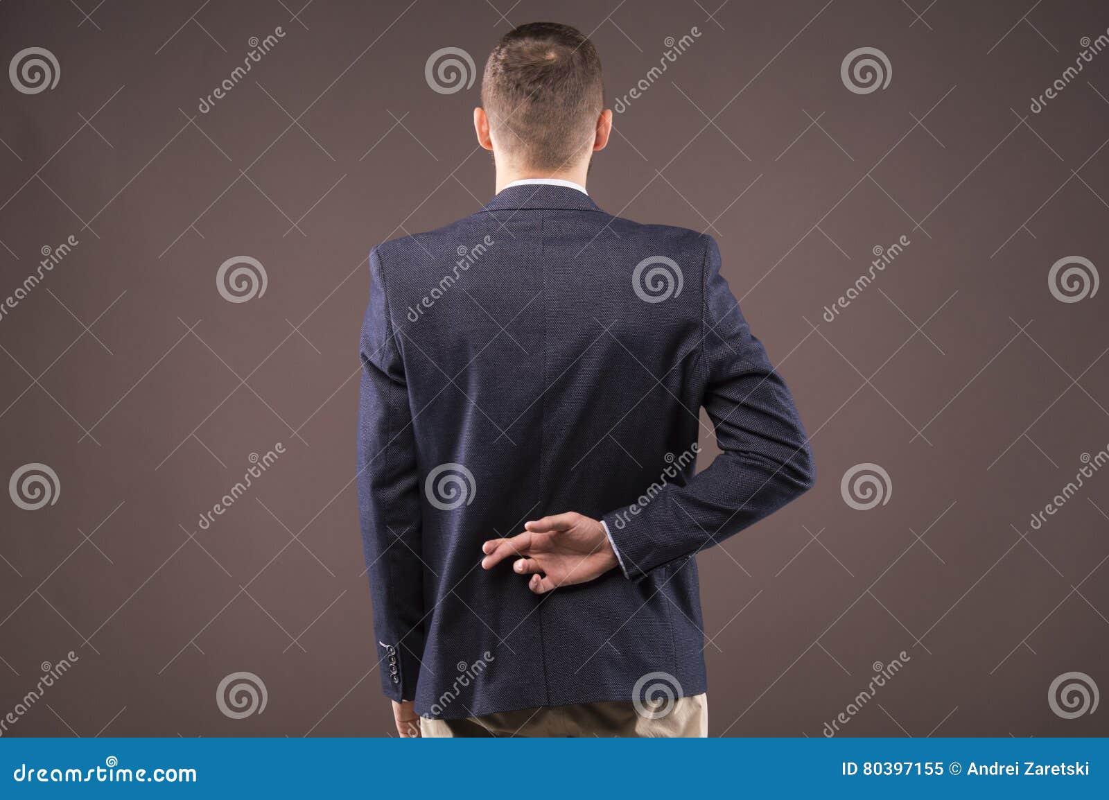 Mężczyzna w kostiumu krzyżował jego palce za jego z powrotem