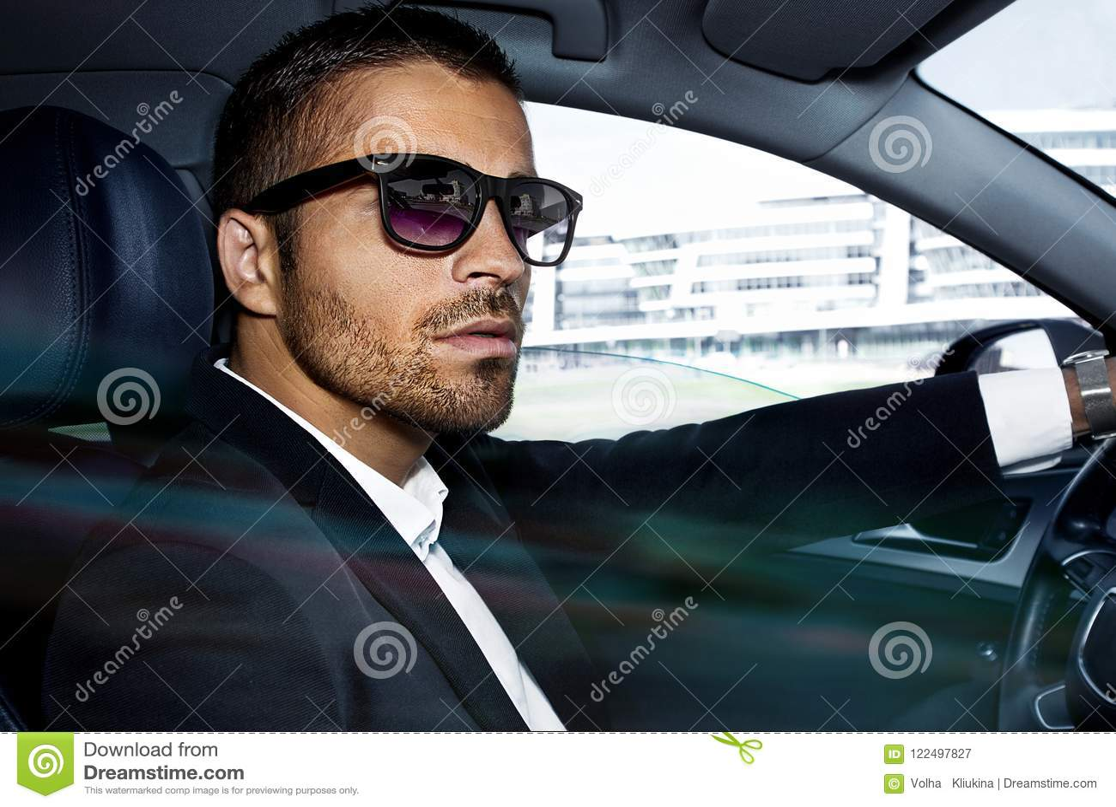 Mężczyzna w kostiumu siedzi przy kołem samochód