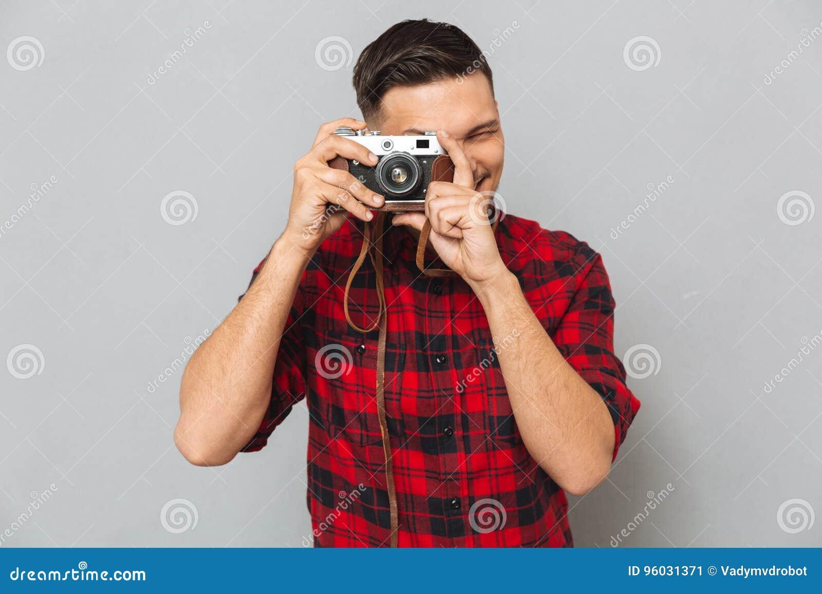 Mężczyzna w koszulowej robi fotografii na retro kamerze