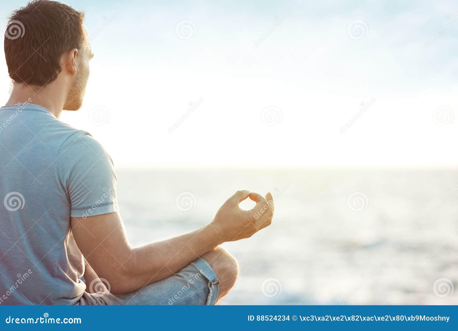 Mężczyzna w medytaci blisko morza