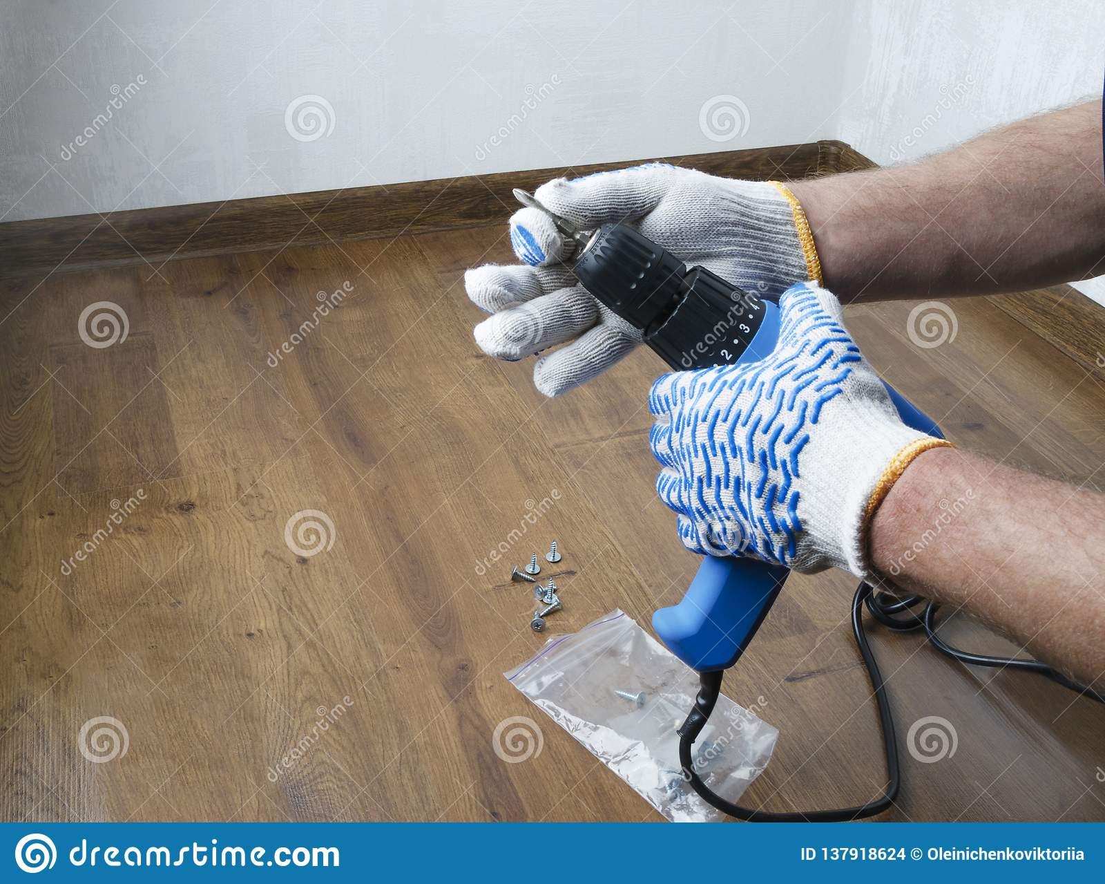 Mężczyzna w rękawiczkach przygotowywa dla odświeżania, stawia w niektóre świderu kawałku Pojęcie naprawy w domu