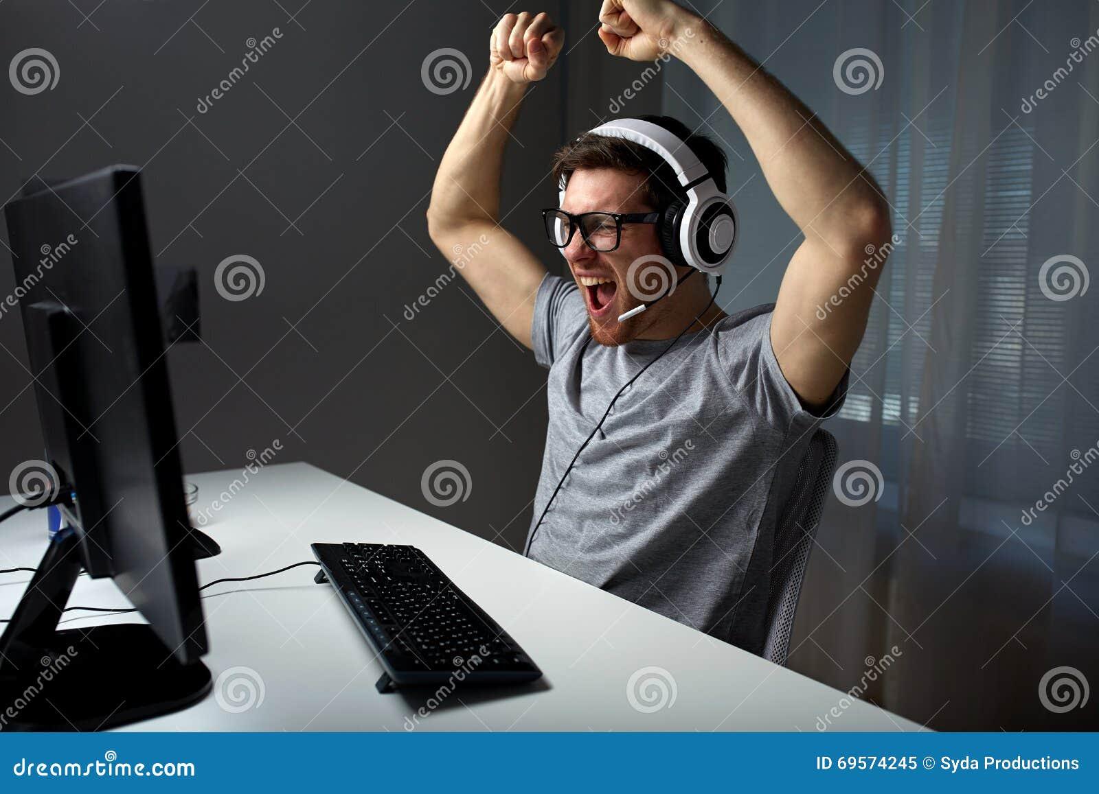 Mężczyzna w słuchawki bawić się komputerową wideo grę w domu