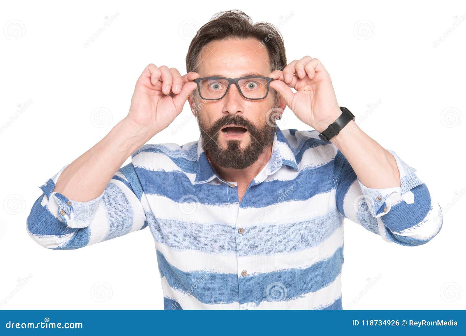 Mężczyzna w szkłach z szokującym, zadziwiającym wyrażeniem odizolowywającym na białym tle, Sfrustowany brodaty młody przystojny m