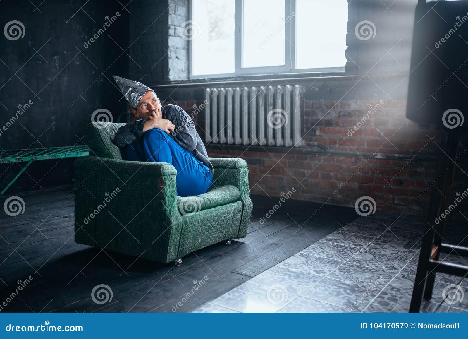 Mężczyzna w tinfoil hełma zegarku TV, umysł ochrona