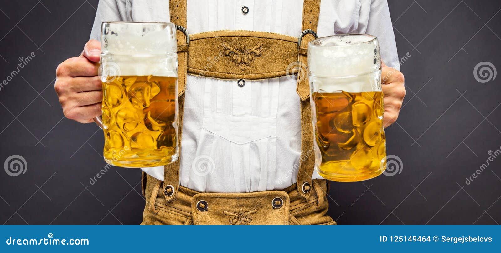 Mężczyzna w tradycyjnego bavarian mienia odzieżowym kubku piwo