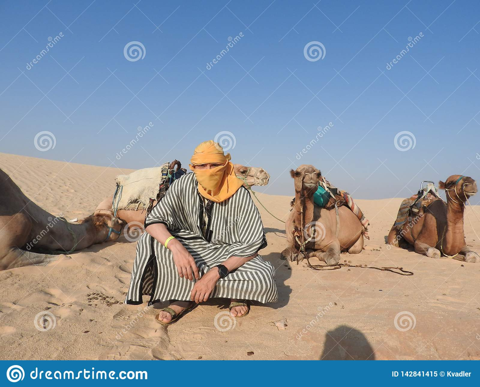 Mężczyzna w turbanie, twarz zakrywająca, z wielbłądem w saharze