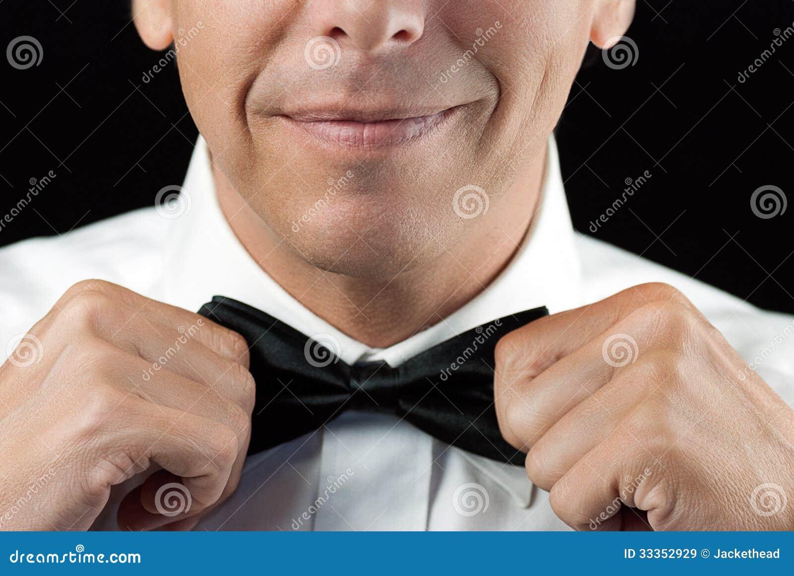 Mężczyzna W Tux Prostuje Bowtie, Dwa ręki
