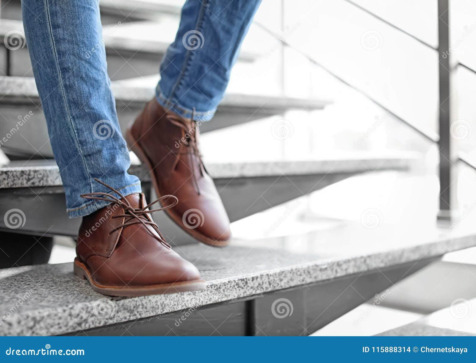 Mężczyzna wewnątrz w eleganckich butach chodzi w dół schodki
