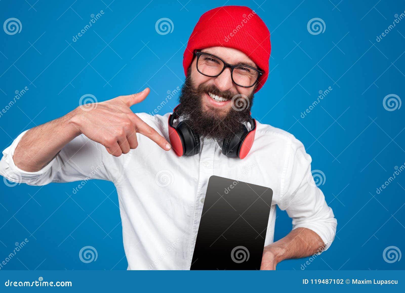 Mężczyzna wskazuje przy pastylką w hełmofonach