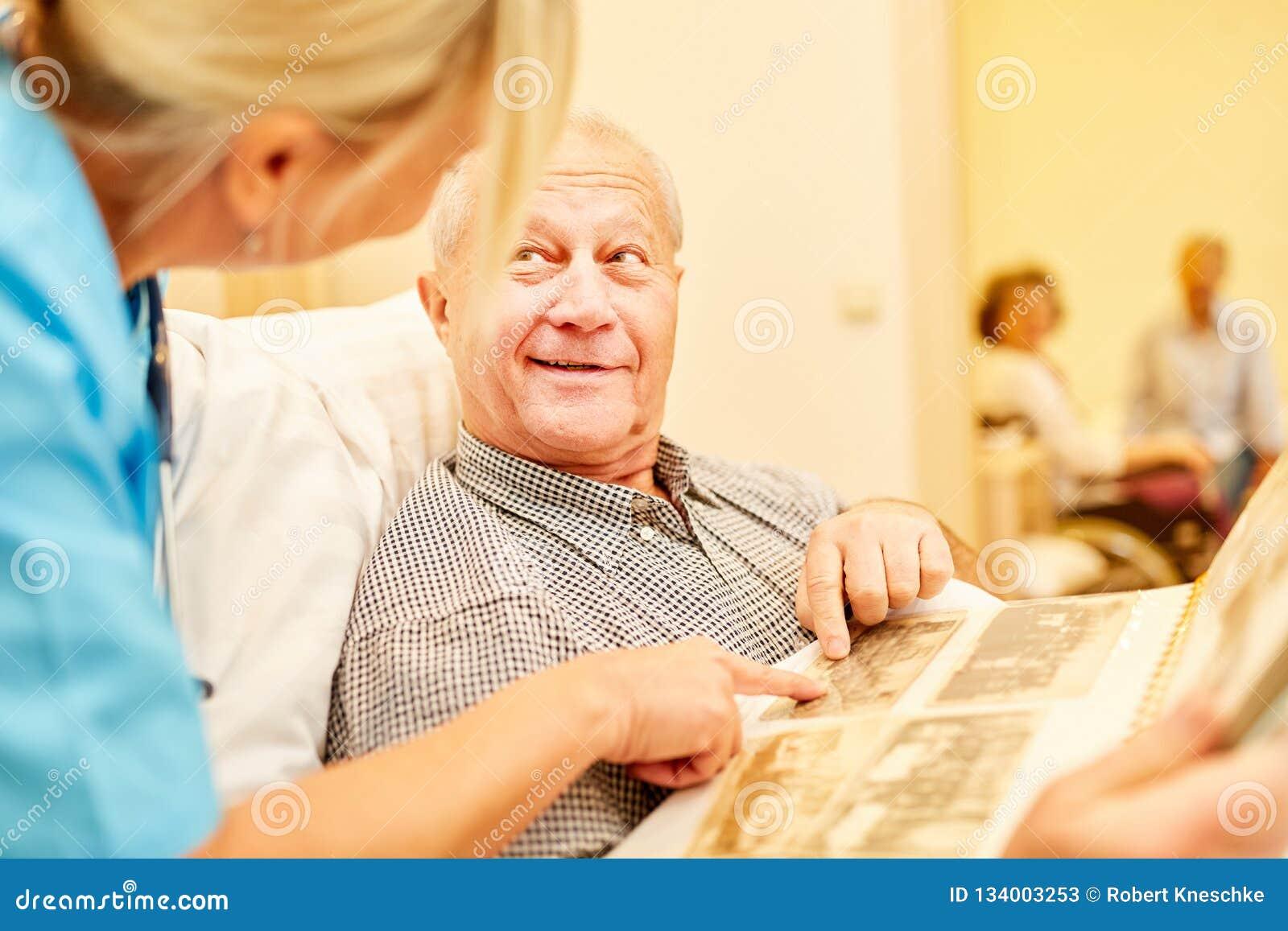 Mężczyzna z Alzheimer spojrzeniami przy albumem fotograficznym