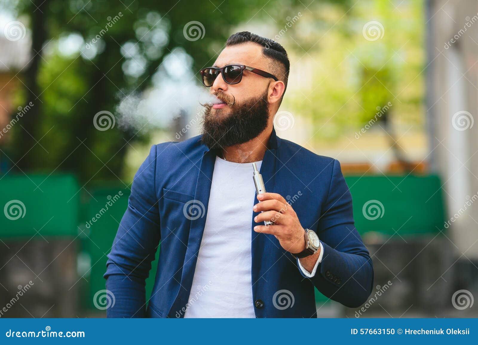 Mężczyzna z brodą dymi elektronicznego papieros