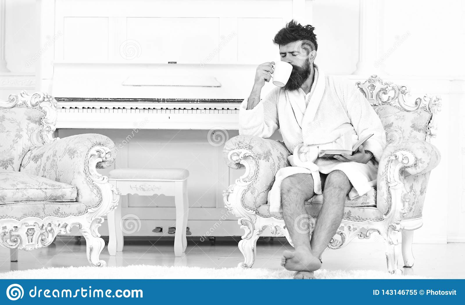 Mężczyzna z brodą i wąsy cieszy się ranek podczas gdy siedzący na luksusowym karle Elita czasu wolnego pojęcie Mężczyzna śpiący w
