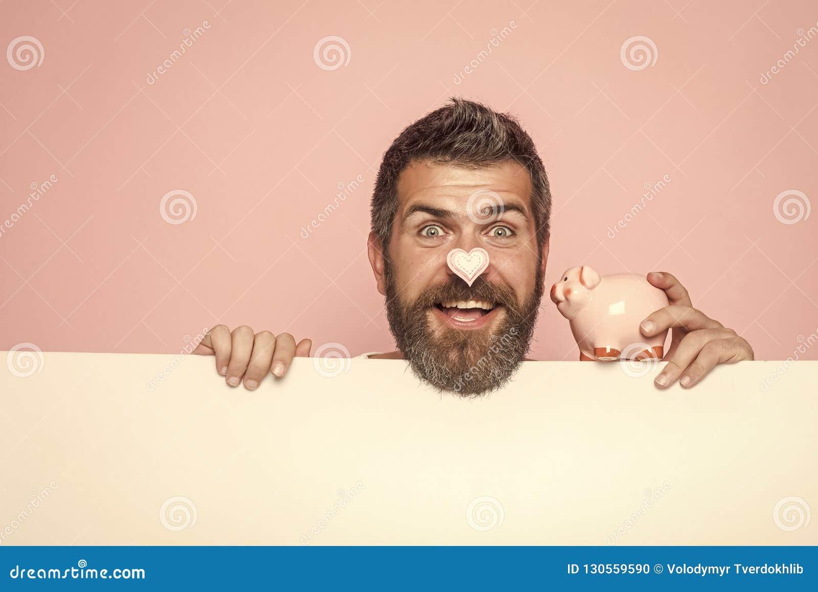 Mężczyzna z brodą na szczęśliwym twarz chwyta prosiątka banku, moneybox