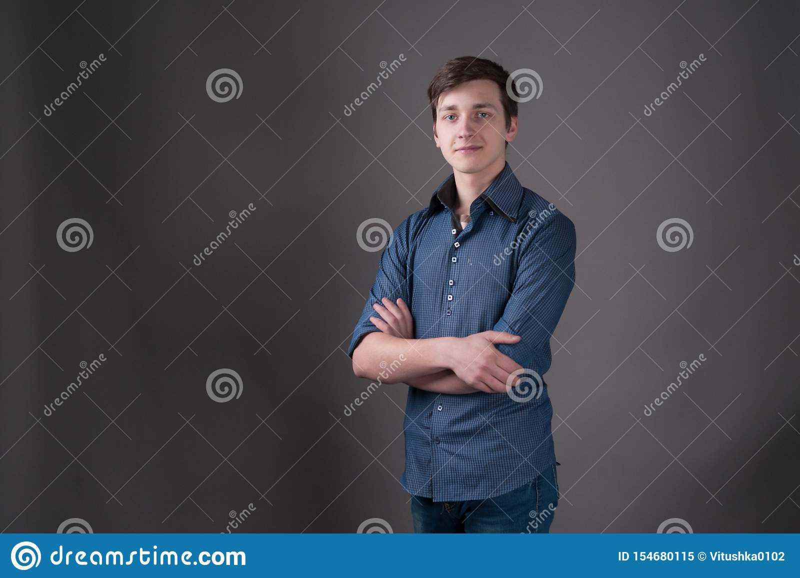 Mężczyzna z ciemnym włosy w błękitnej koszulowej pozycji z krzyżować rękami