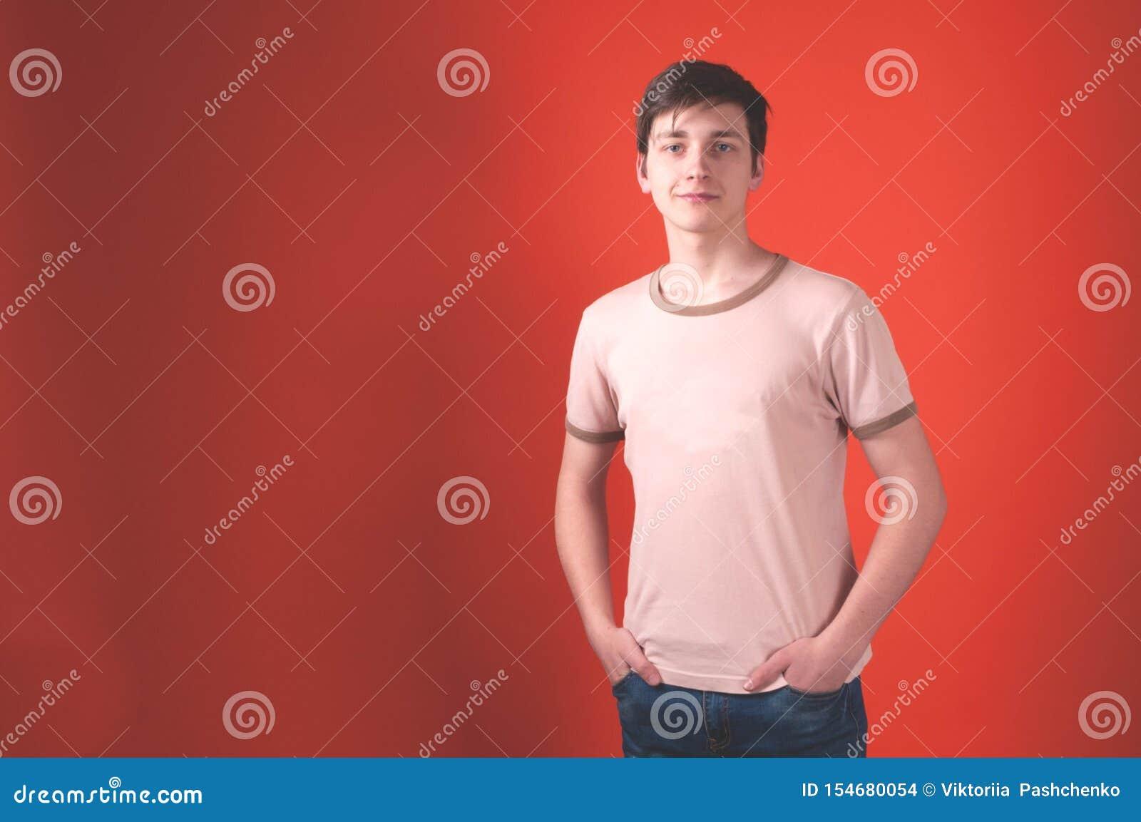 Mężczyzna z ciemnym włosy w beżowej koszulki pozycji z rękami w kieszeniach na koralowym tle