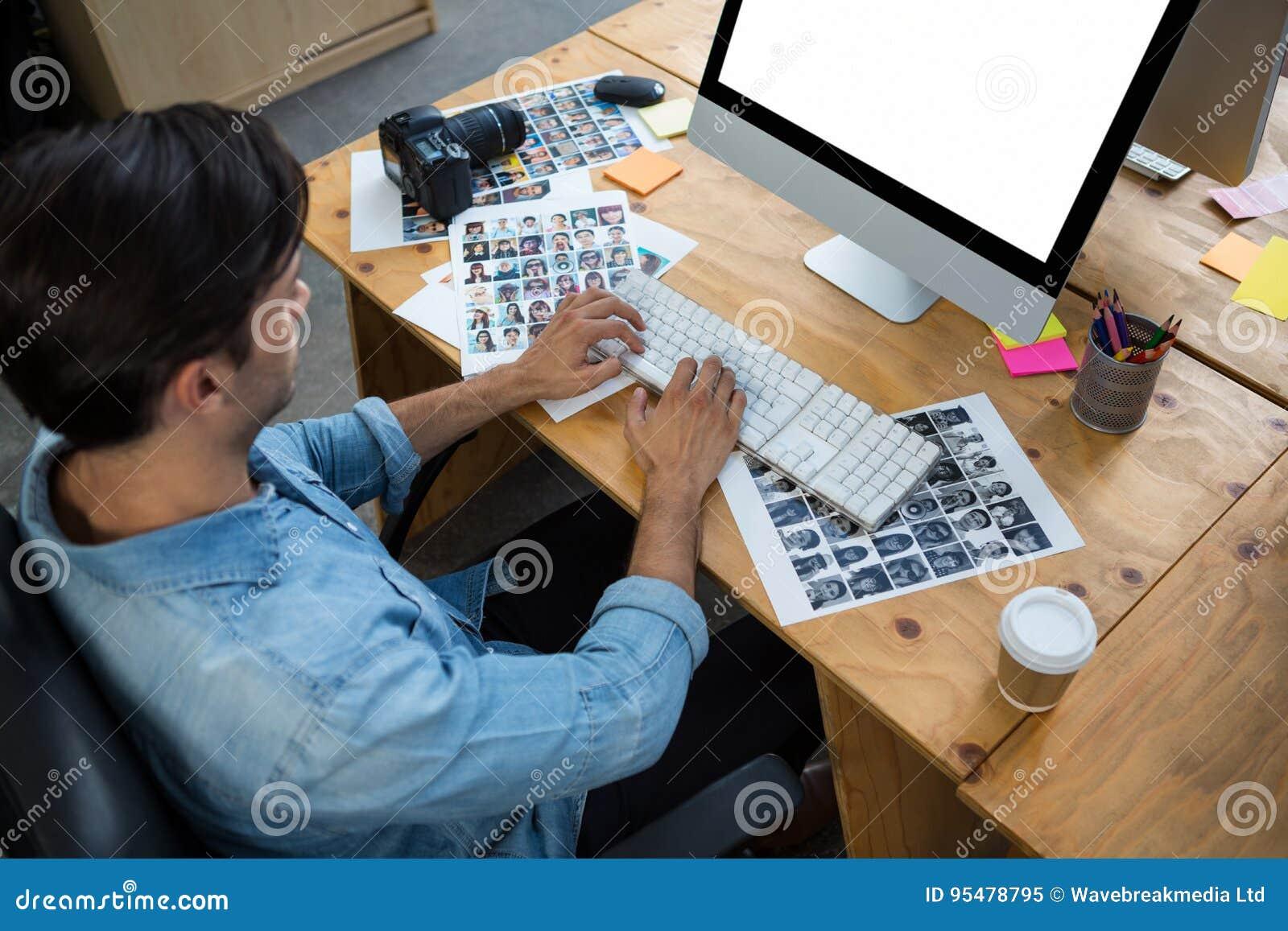 Mężczyzna z fotografiami pracuje na komputerze stacjonarnym