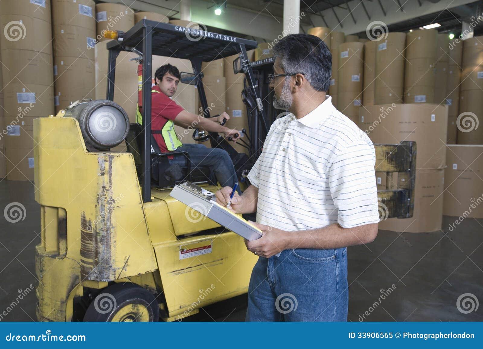 Mężczyzna Z kolegą W Forklift śladzie Przy fabryką
