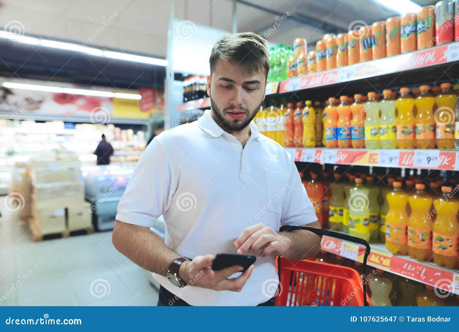 Mężczyzna z kosza spojrzeniami przy telefonem podczas gdy robiący zakupy przy supermarketem Robić zakupy w sklepie