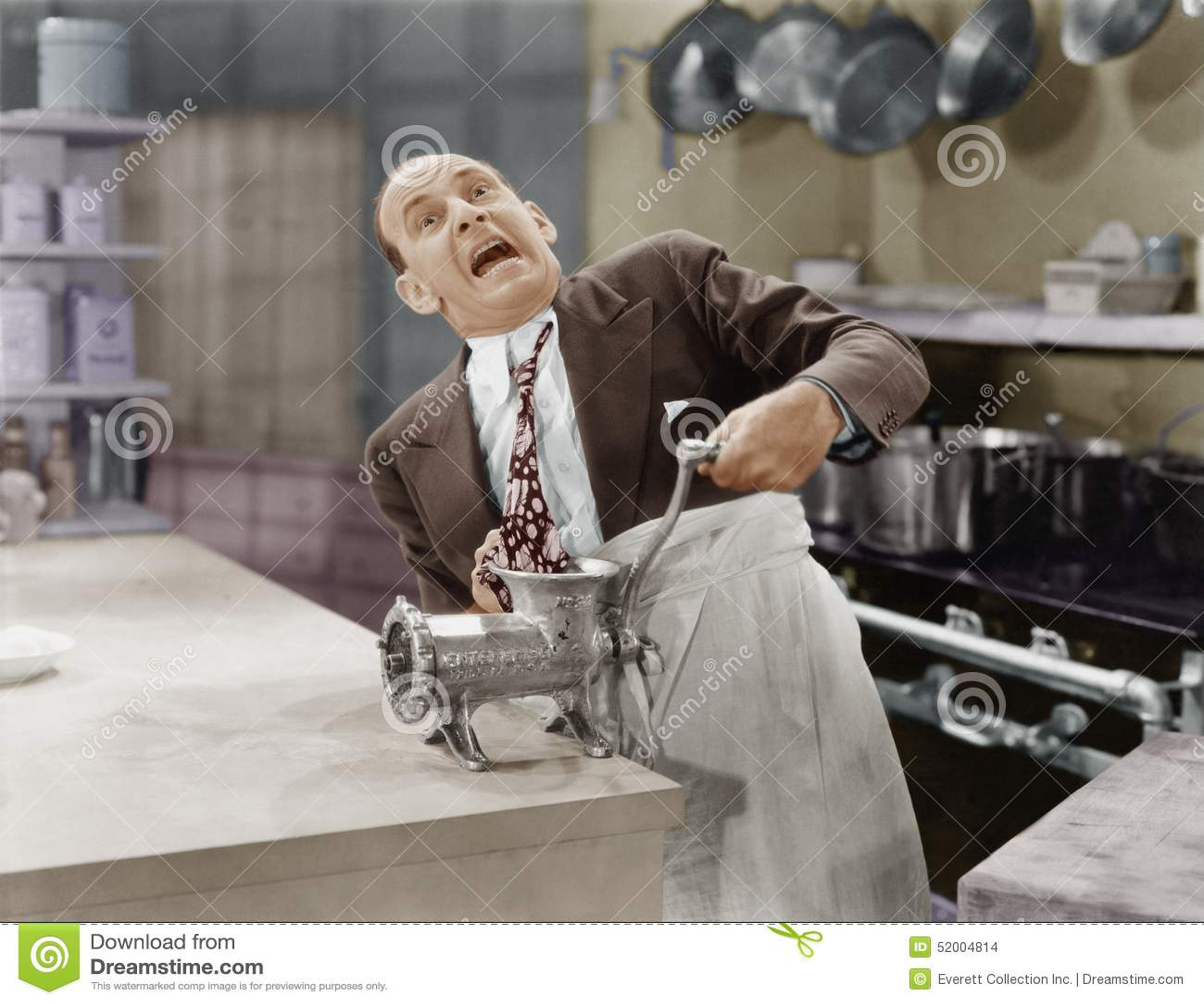 Mężczyzna z krawatem wtykającym w maszynka do mięsa