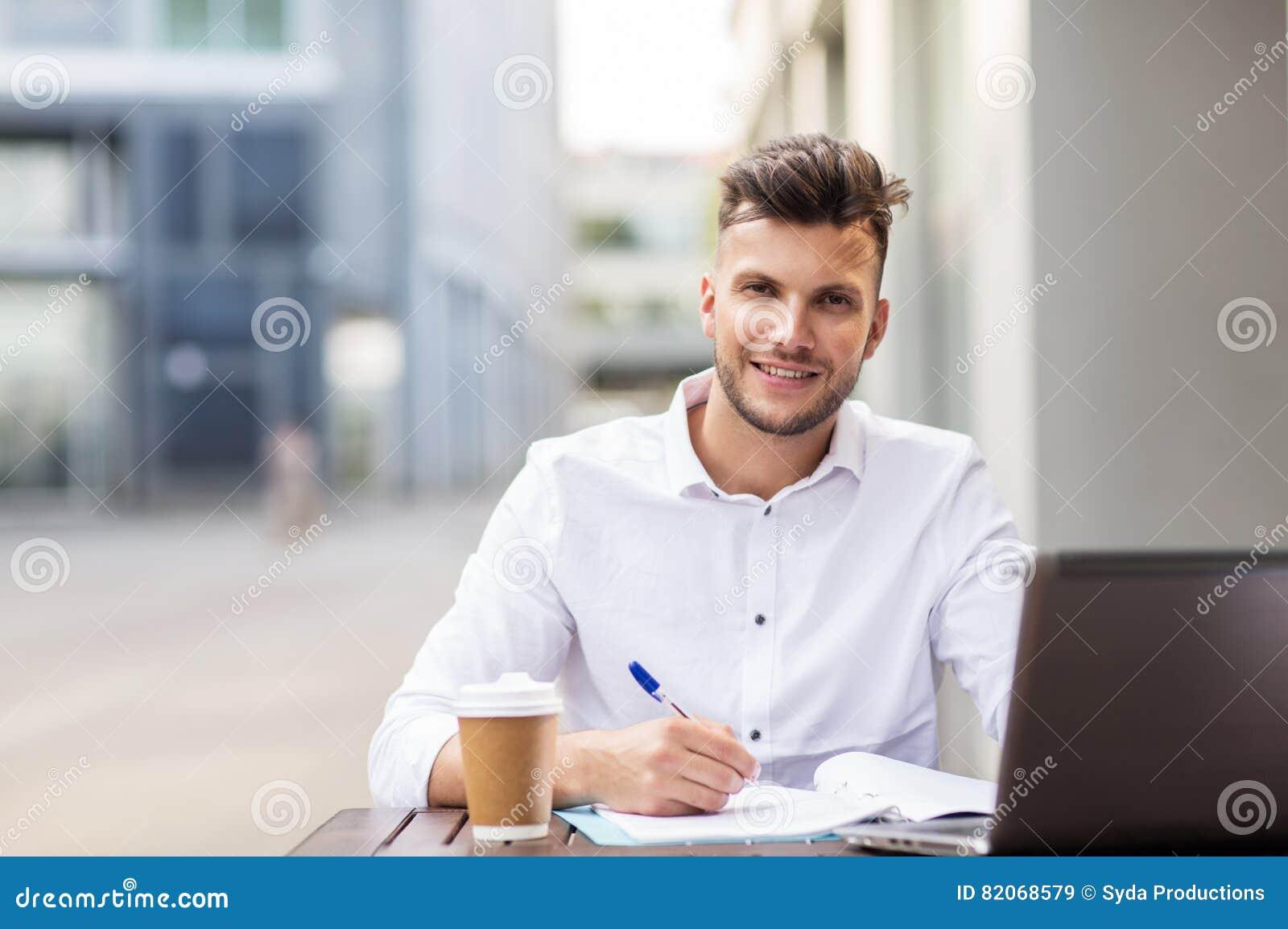 Mężczyzna z laptopem i kawą przy miasto kawiarnią