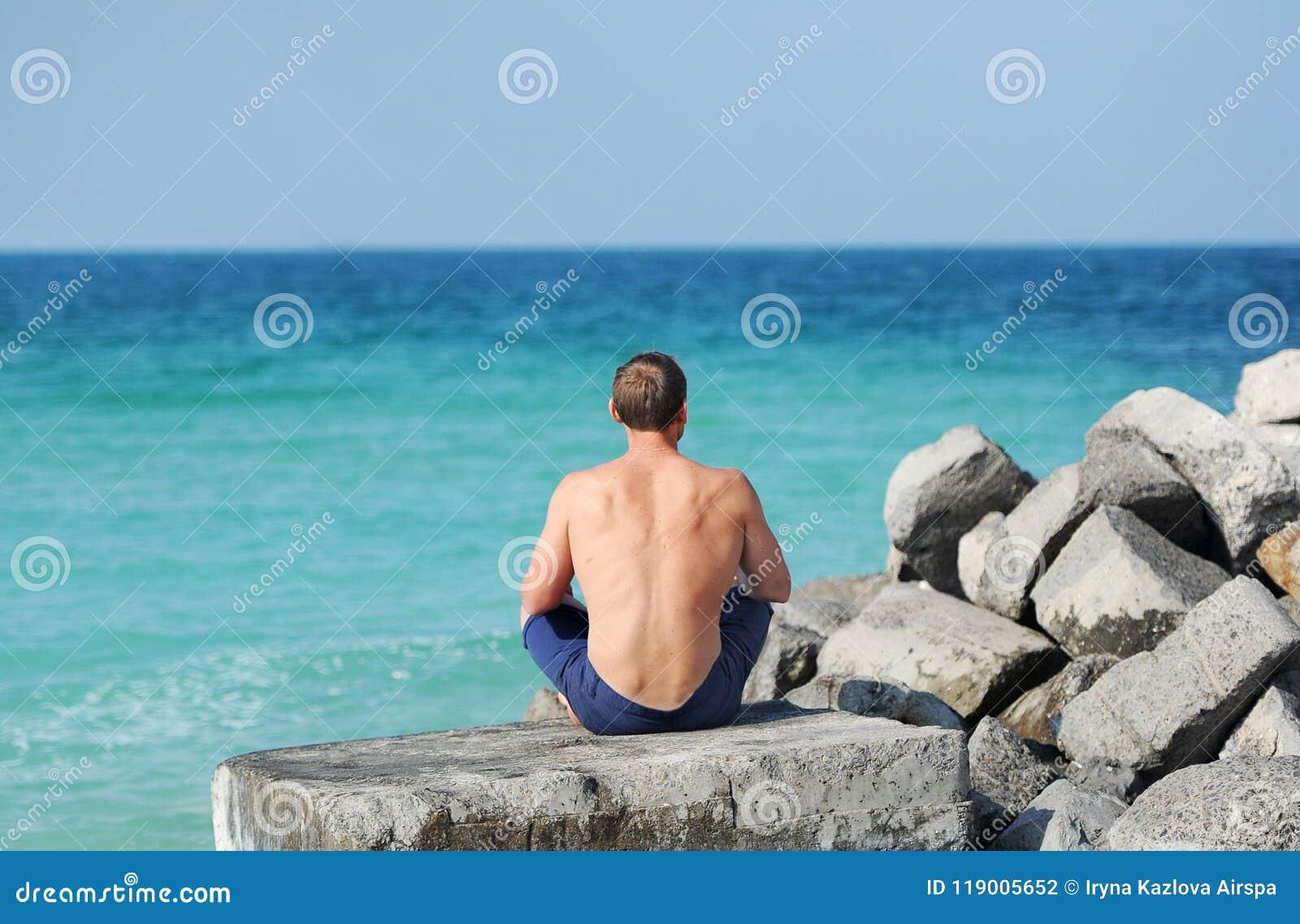 Mężczyzna z nagim półpostaci obsiadaniem na kamieniu z jej z powrotem patrzeć morze