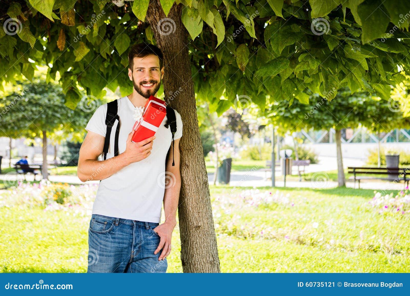 Mężczyzna z plecakiem i prezentem obok drzewa