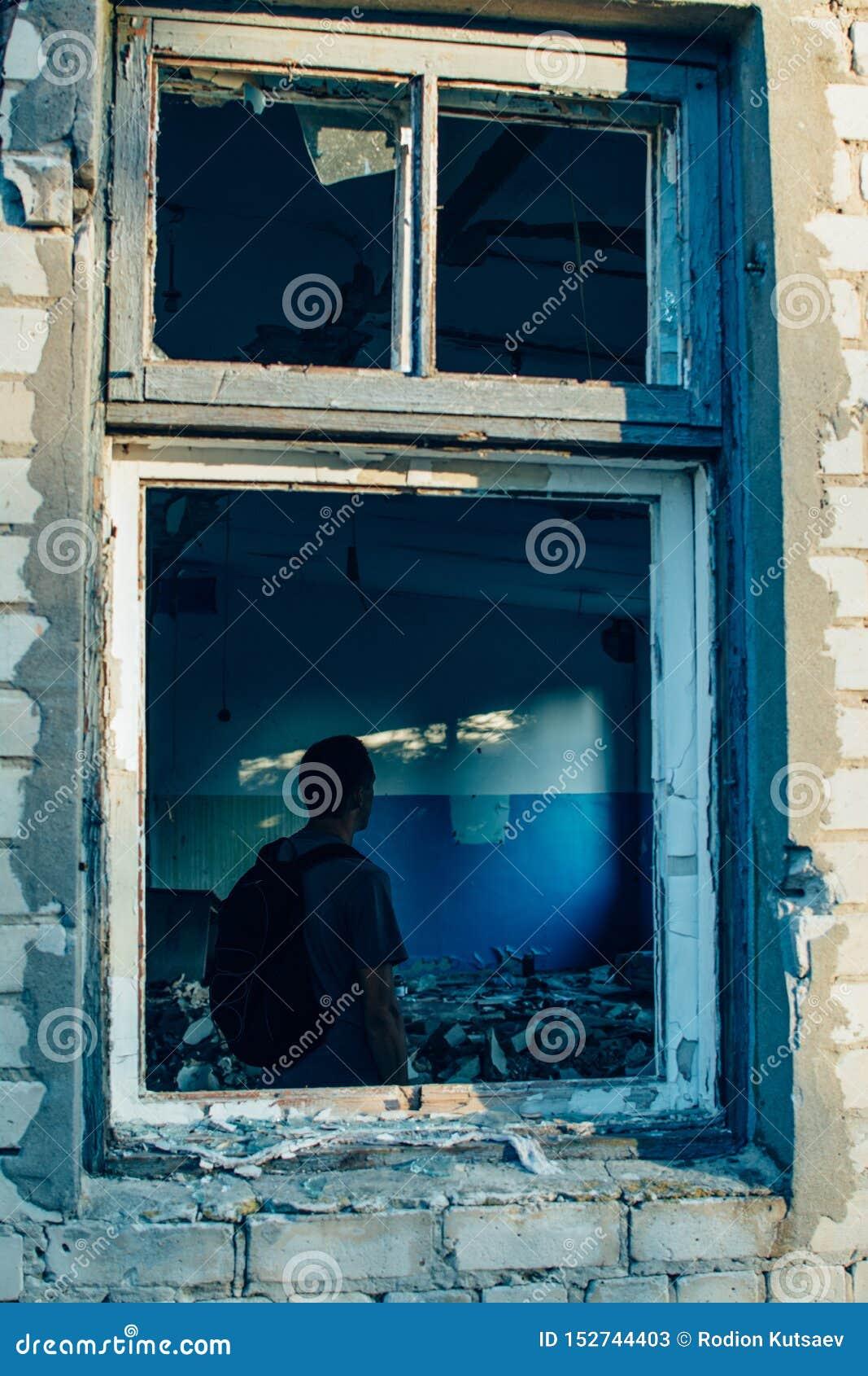 Mężczyzna z plecakiem w rujnującej zniszczonego starego budynku nadokiennej ramie