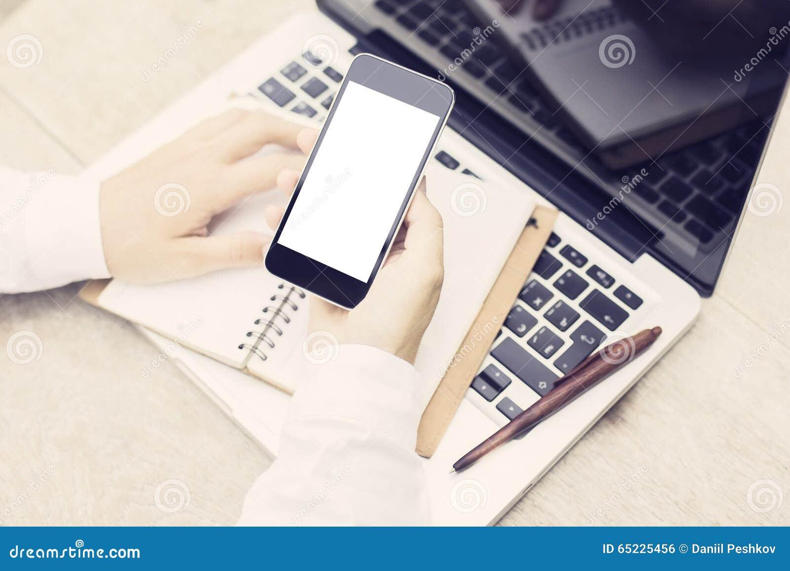 Mężczyzna z pustym telefonem komórkowym, laptopem i dzienniczkiem na drewnianym stole, moc
