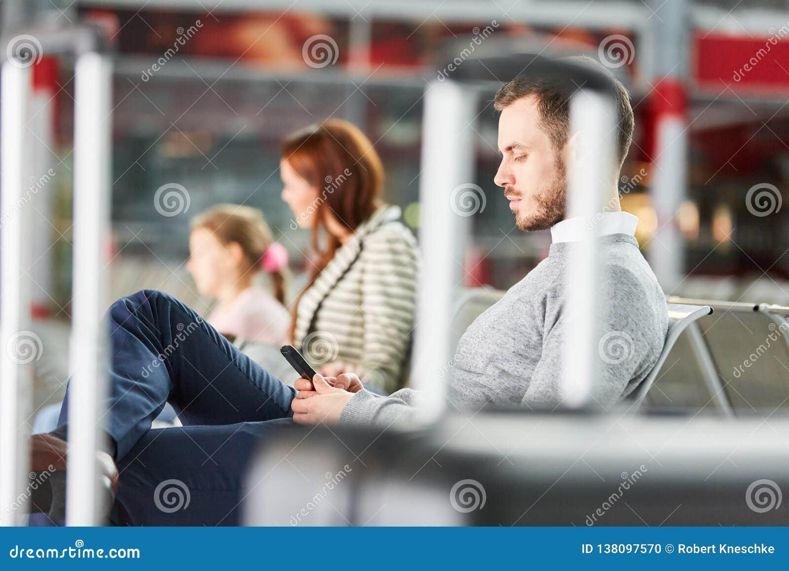 Mężczyzna z smartphone czeka w lotniskowym spoczynkowym terenie
